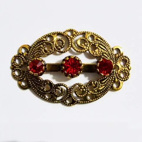 Broche oval dorado piedras rojas